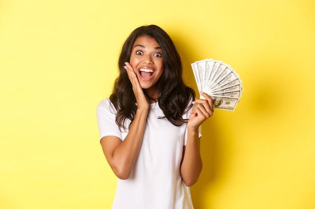 Afbeelding van een opgewonden gelukkig meisje dat geld wint en verbaasd glimlacht terwijl ze over een gele achtergrond staat