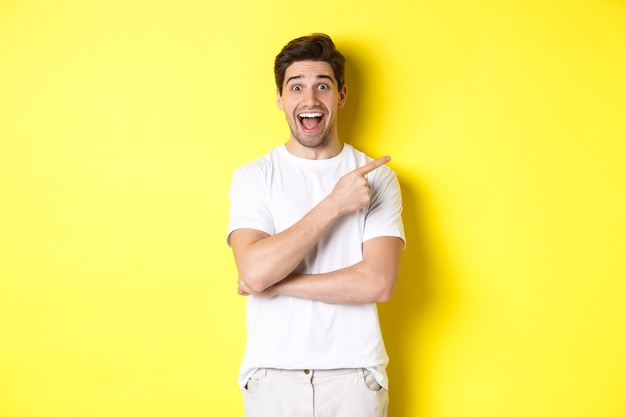Afbeelding van een opgewonden glimlachende man die zwarte vrijdagaanbiedingen toont, met de vinger naar rechts wijst en verbaasd kijkt, staande over de gele muur