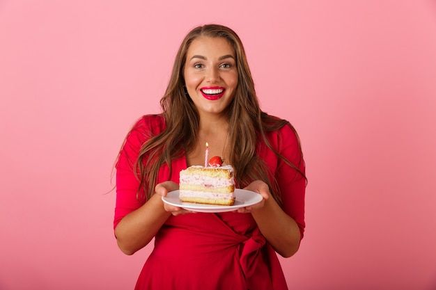 Afbeelding van een opgewonden hongerige jonge vrouw die over de roze cake van de muurholding wordt geïsoleerd.