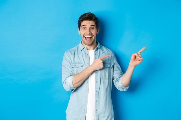 Afbeelding van een opgewonden knappe man in een casual outfit, die advertenties toont, met de vingers naar de kopieerruimte wijst en glimlacht, staande tegen een blauwe achtergrond