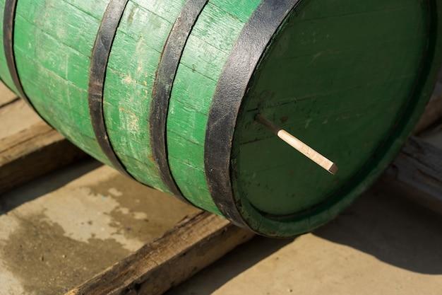 Afbeelding van een oud eiken wijnvat op de achtergrond van een landelijke binnenplaats.