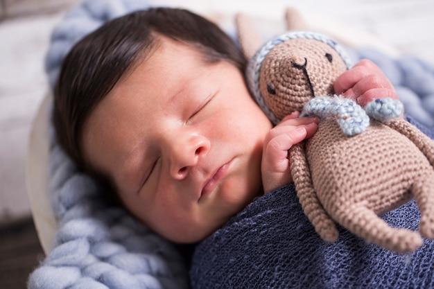Afbeelding van een pasgeboren braziliaanse baby gekruld slapen in een deken
