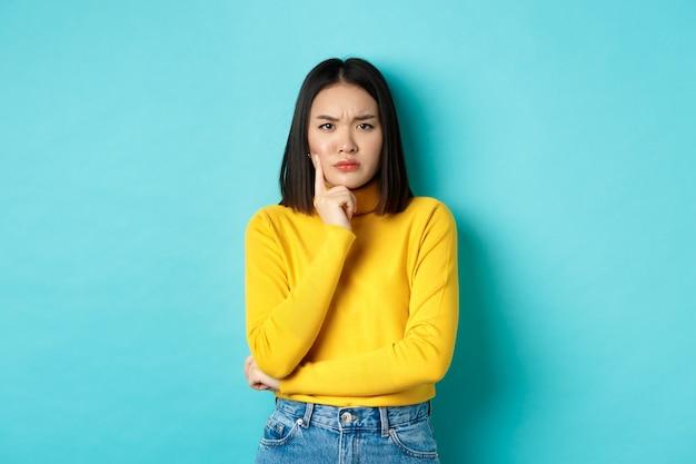Afbeelding van een peinzende en serieuze aziatische vrouw die de kin aanraakt, fronst en verbaasd naar de camera staart, een moeilijke keuze maakt en over een blauwe achtergrond staat.
