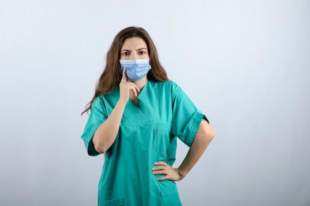 Afbeelding van een peinzende mooie verpleegster in groen uniform die wegkijkt