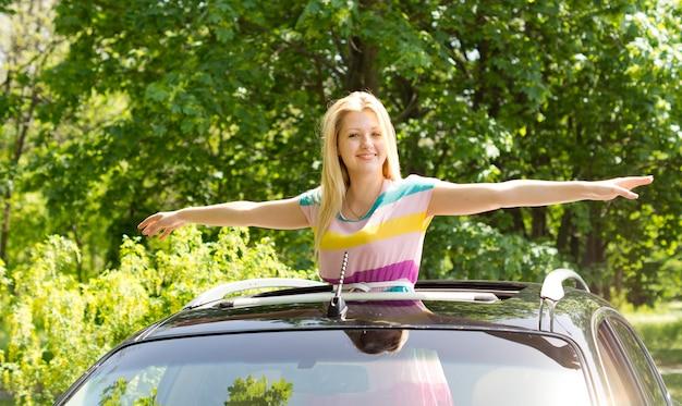 Afbeelding van een prachtig jong vrouwtje dat haar handen spreidt als een vogel buiten een rijdende auto.
