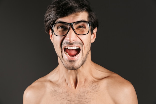 Afbeelding van een schreeuwende emotionele jonge man geïsoleerd met een bril.