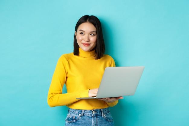 Afbeelding van een stijlvolle koreaanse vrouw die op een laptop werkt en wegkijkt met een dromerige glimlach, staande met de computer tegen een blauwe achtergrond
