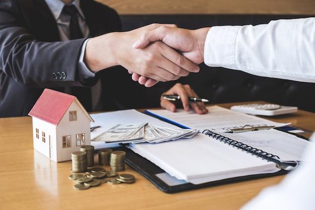 Afbeelding van een succesvolle deal van onroerend goed, makelaar en klant die handen schudden na ondertekening van het contract goedgekeurde aanvraagformulier, betreffende hypothecaire leningaanbieding en huisverzekering
