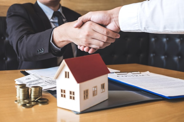 Afbeelding van een succesvolle deal van onroerend goed, makelaar en klant die handen schudden na ondertekening van het contract goedgekeurde aanvraagformulier, betreffende hypotheekaanbieding en huisverzekering