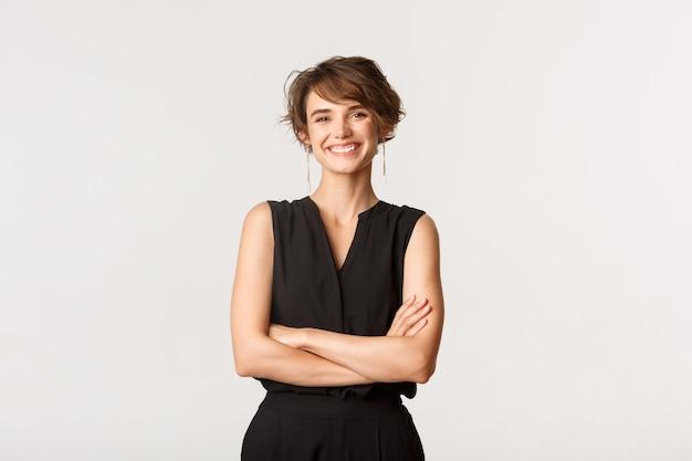 Afbeelding van een succesvolle, gelukkige zakenvrouw lachend met gekruiste armen, staande witte achtergrond.