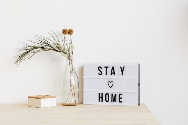 Afbeelding van een tafel met bloemen en poster erop thuis