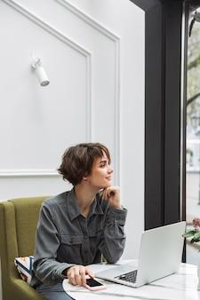 Afbeelding van een tevreden jonge, mooie zakenstudentvrouw die binnenshuis in een café zit met behulp van een laptopcomputer die samenwerkt met een mobiele telefoon.