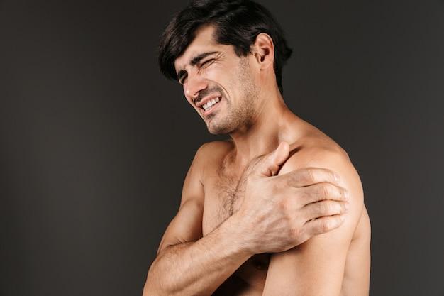 Afbeelding van een trieste ontevreden jonge man met pijn in de arm geïsoleerd poseren.