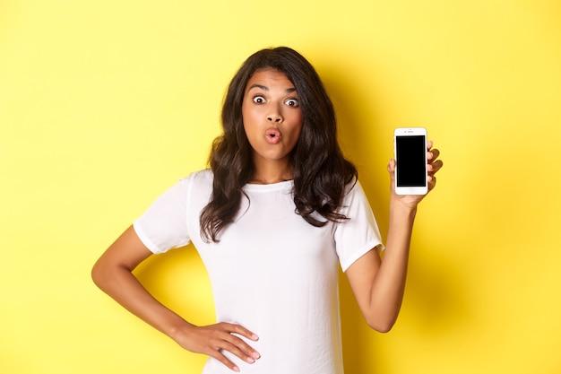 Afbeelding van een verbaasd afrikaans-amerikaans meisje dat er gefascineerd uitziet en een smartphonescherm laat zien
