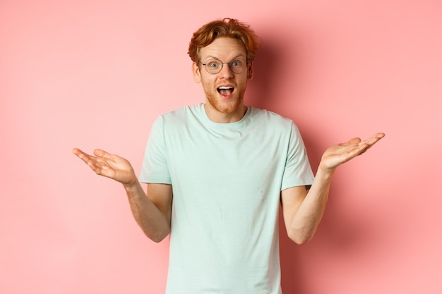 Afbeelding van een verbaasde roodharige man met een bril die zijn handen zijwaarts spreidt en er onder de indruk uitziet terwijl hij voor hem staat.