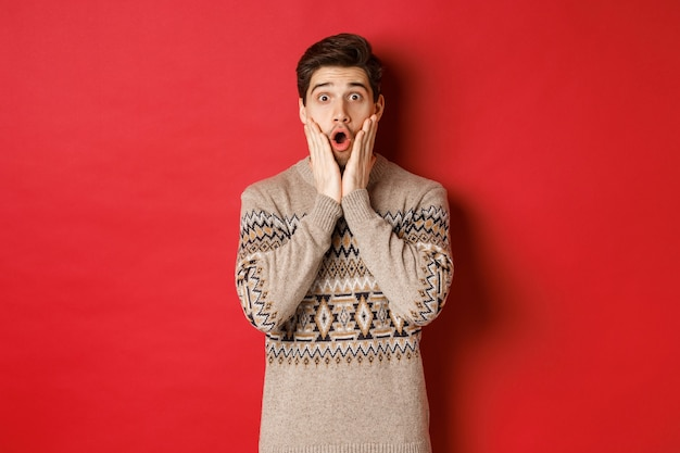 Afbeelding van een verraste knappe kerel die reageert op een coole nieuwjaarspromo-aanbieding, verbaasd naar adem snakkend, een kersttrui draagt, staande over een rode achtergrond