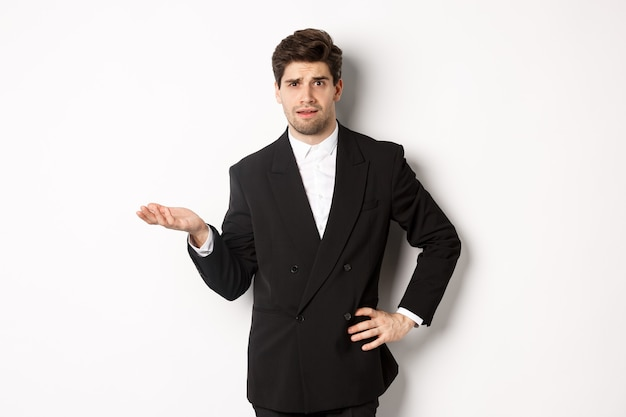 Afbeelding van een verwarde knappe man in een formeel pak, hand opstekend en schouderophalend, kan iets niet begrijpen, staande tegen een witte achtergrond.