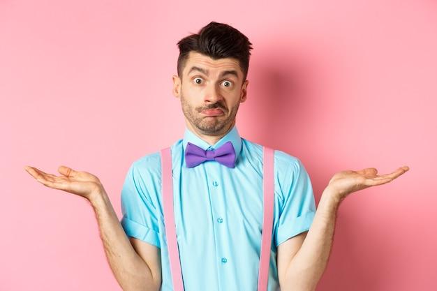 Afbeelding van een verwarde man in vlinderdas en bretels weet niets, haalt schouders op en kijkt geen idee, staande over roze achtergrond.