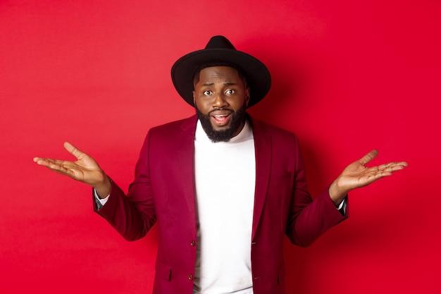 Afbeelding van een verwarde zwarte man die een vraag stelt, zijn handen zijwaarts spreidt en de camera geen idee heeft, staande tegen een rode achtergrond