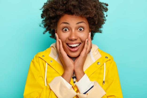 Afbeelding van een vrij gekrulde vrouw met verbaasde blije uitdrukking, draagt gele regenjas, breed lacht, ogen wijd geopend van verwondering,