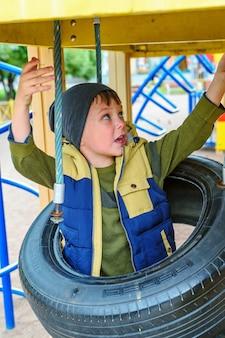 Afbeelding van een vrolijk kind van vijf jaar dat plezier heeft op een buitenspeeltuin.