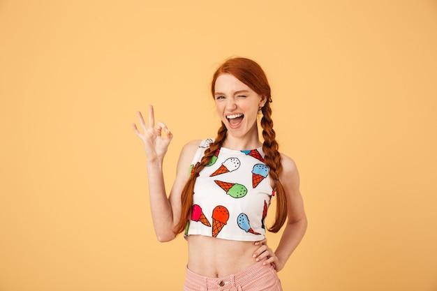 Afbeelding van een vrolijke jonge mooie roodharige vrouw gekleed in een met ijs bedrukt t-shirt poseren geïsoleerd over een gele muur met een goed gebaar.