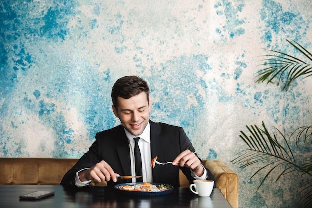 Afbeelding van een vrolijke knappe jonge zakenman zitten in café ontbijten of dineren.