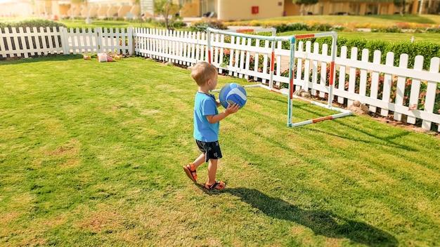Afbeelding van een vrolijke lachende jongen die een voetbalbal in handen houdt en op de kinderspeelplaats in het park rent