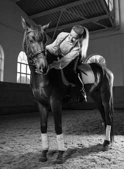 Afbeelding van een vrouw die een volbloed paard berijdt. de achtergrond is een race-arena. gemengde media