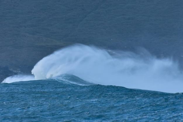 Afbeelding van een wilde oceaangolf die op de kust crasht