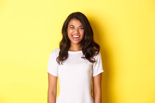 Afbeelding van een zorgeloos afrikaans-amerikaans meisje in een wit t-shirt met een lachende en knipogende lach van een blije stan...