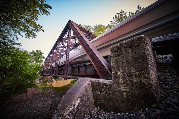 Afbeelding van einde van metalen brug voor trein met vervaging van passerende trein