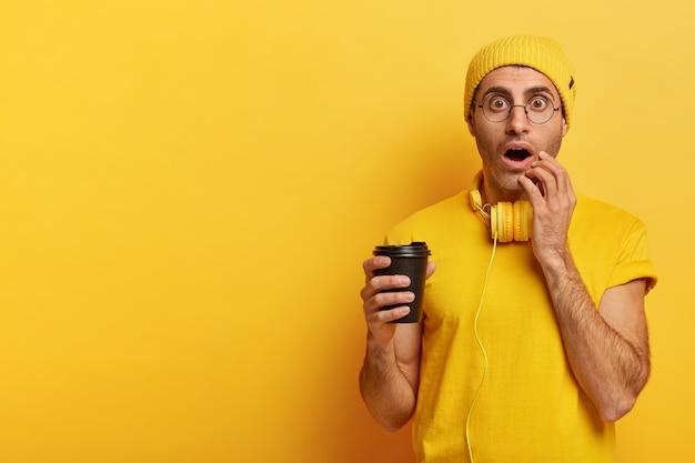 Afbeelding van emotionele jongere houdt wegwerpkop koffie vast, staart met wijd geopende ogen, kan ogen niet geloven, draagt gele hoed