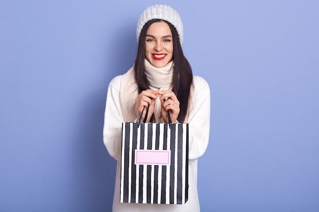 Afbeelding van energieke positieve dame met zwart haar en rode lippen, aanwezig in papieren gestreepte tas, glimlachend oprecht