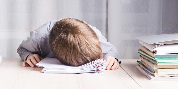 Afbeelding van erg moe schooljongen of student zijn hoofd geklemd