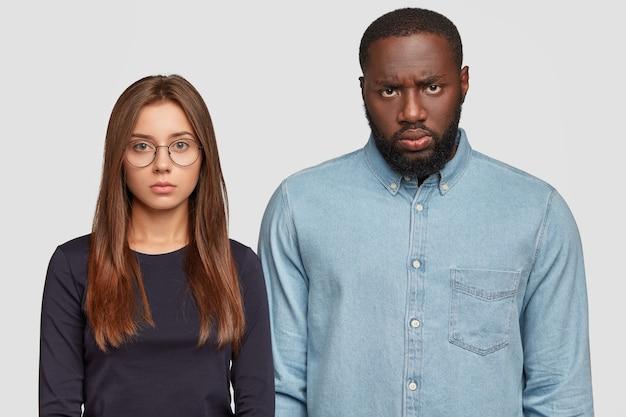 Afbeelding van ernstige sombere interraciale vrouw en man kijken direct