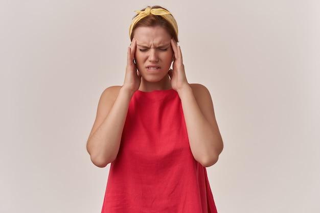 Afbeelding van europese bruinharige jeugd. vrouw in stijlvolle trendy rode jurk en gele bandana met armen aanraken van gezicht en ogen gesloten emotie benadrukt in pijn hoofdpijn poseren