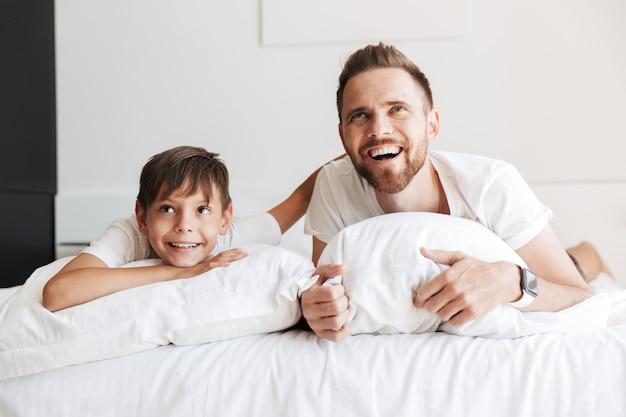 Afbeelding van europese vader en zoon lachen, liggend op bed met wit linnen thuis en op zoek naar boven