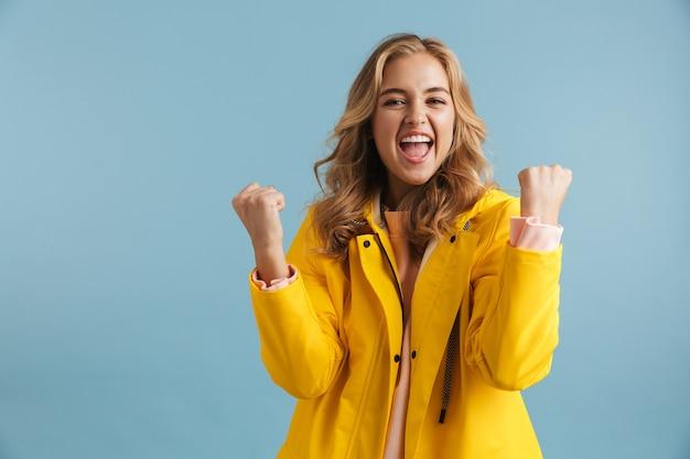 Afbeelding van europese vrouw 20s dragen gele regenjas schreeuwen van vreugde