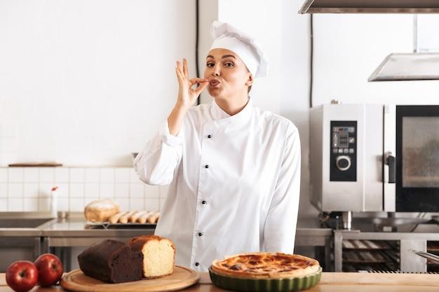 Afbeelding van europese vrouw chef-kok dragen witte uniform, poseren in de keuken in het café met gebakken goederen