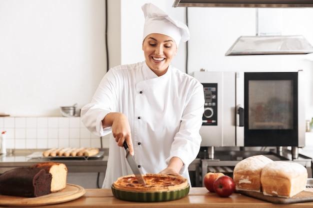 Afbeelding van europese vrouw chef-kok dragen witte uniforme appeltaart houden, tijdens het koken in de keuken bij de bakkerij
