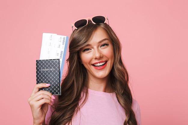 Afbeelding van europese vrouw met mooie bruine sloten glimlachend terwijl paspoort en vliegtickets, geïsoleerd op roze achtergrond
