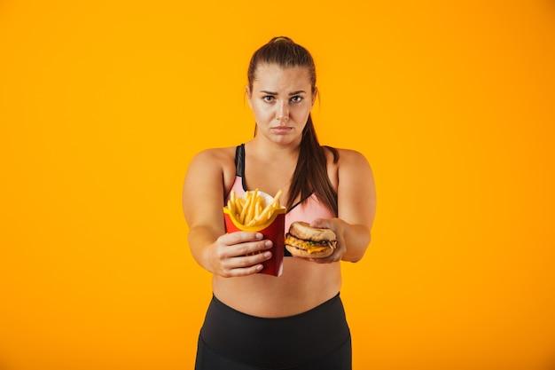 Afbeelding van europese vrouw met overgewicht in trainingspak doet stop gebaar terwijl sandwich en frietjes, geïsoleerd op gele achtergrond