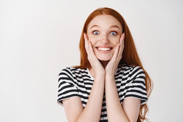Afbeelding van extreem blije en verraste jonge vrouw met rood haar, gezicht aanraken en verbaasd glimlachen, verrassingsgeschenk ontvangen, witte muur