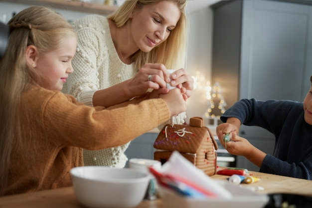 Afbeelding van familie kersttijd besteden aan het verfraaien van peperkoek huis