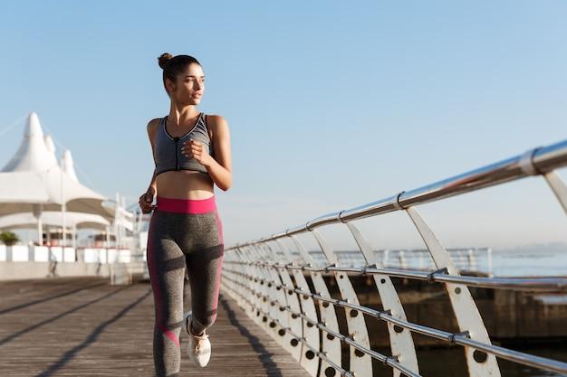 Afbeelding van fit en gezond vrouw joggen in de ochtend, zee kijken tijdens training.