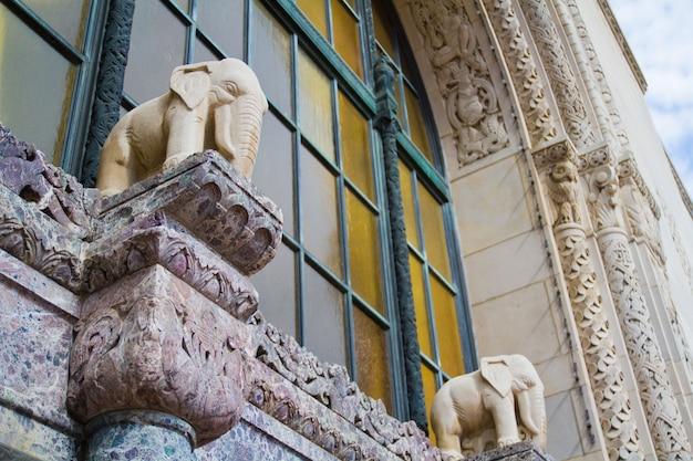 Afbeelding van foto van lansing-gebouw met beelden van witte olifanten voor een verroest raam