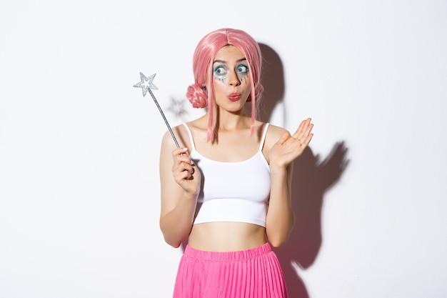 Afbeelding van geamuseerd schattig meisje met roze pruik en lichte make-up, verkleed als fee voor halloween-feest, toverstaf vasthouden en er opgewonden uitzien, staand.