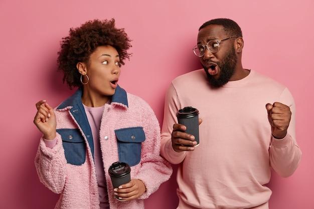Afbeelding van geamuseerde zorgeloze zwarte jonge vrouw en man dansen vrolijk, drinken afhaalkoffie, uiten positieve emoties