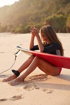 Afbeelding van gebruinde sportieve gezonde vrouw gebruikt surfplank met beenriem, klaar om te surfen op het strand, houdt de handen bij elkaar